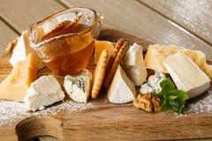 Prato do queijo do gosto em uma placa de madeira Alimento para o vinho e rom?ntico, guloseimas do queijo em uma tabela r?stica de foto de stock