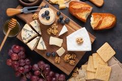 Prato do queijo do gosto em uma placa de pedra escura Alimento para o vinho e data romântica, guloseimas do queijo em um fundo co foto de stock royalty free