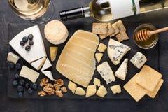 Prato do queijo do gosto em uma placa de pedra escura Alimento para o vinho e data romântica, guloseimas do queijo em um fundo co fotos de stock