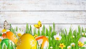 Prato idilliaco della molla con le uova di Pasqua e le farfalle Immagini Stock
