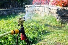 Prato inglese d'innaffiatura dell'impianto di irrigazione del giardino Spruzzatore d'innaffiatura Immagine Stock