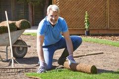 Prato inglese di Laying Turf For del giardiniere di paesaggio nuovo immagini stock