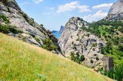 Prato inglese verde contro l'alta roccia ed il cielo blu con le nuvole, torre Fotografia Stock Libera da Diritti
