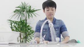 Prato novo asiático da lavagem do menino na cozinha em casa, conceito do estilo de vida vídeos de arquivo