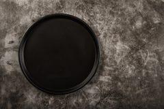 Prato preto em um fundo cinzento Disposição de pratos pretos em um fundo cinzento Vista de acima fotografia de stock