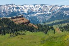 Prato snowcapped delle montagne della collina rossa Immagine Stock