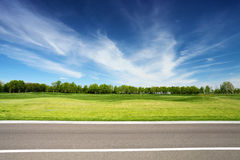 Prato verde con gli alberi e la strada asfaltata Immagini Stock Libere da Diritti