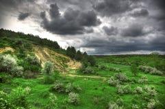 Prato verde con il cielo nuvoloso Immagini Stock