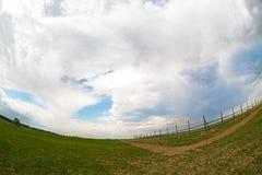 Prato verde con la strada campestre ed il cielo della nuvola Immagini Stock