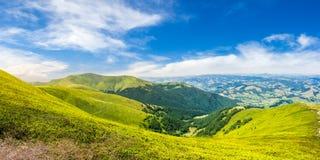 Prato verde di estate nel panorama della montagna Immagine Stock
