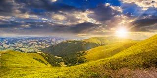 Prato verde di estate nel panorama della montagna al tramonto Immagini Stock