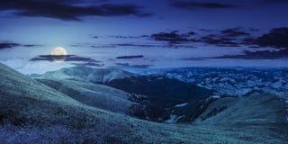 Prato verde di estate nel panorama della montagna alla notte Immagine Stock