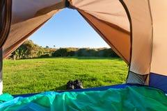 Prato verde e foresta veduti attraverso il portello aperto della tenda Fotografia Stock