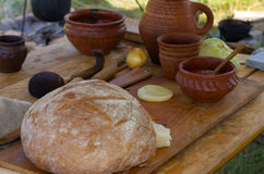 Pratos antigos de madeira e da argila com pão em uma tabela Imagens de Stock Royalty Free