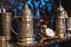 Pratos antigos velhos do vintage, grandes canecas de prata, relógios, foco seletivo Imagem de Stock Royalty Free