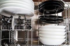 Pratos após a limpeza na máquina da máquina de lavar louça Imagem de Stock