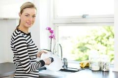 Pratos atrativos da limpeza da mulher foto de stock