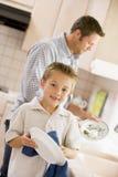 Pratos da limpeza do pai e do filho Imagem de Stock Royalty Free
