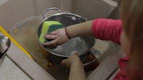 Pratos de lavagem da criança na cozinha Feche acima das mãos das meninas