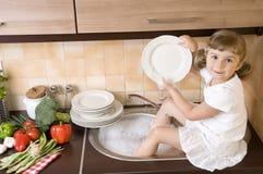 Pratos de lavagem da menina foto de stock