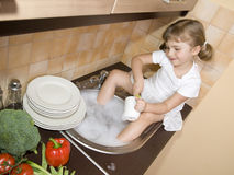 Pratos de lavagem da menina fotografia de stock royalty free