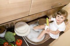 Pratos de lavagem da menina fotos de stock royalty free