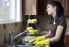 Pratos de lavagem da menina adolescente no dissipador de cozinha Foto de Stock