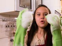 Pratos de lavagem da menina americana asiática com expressão engraçada foto de stock royalty free