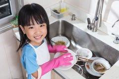 Pratos de lavagem da menina chinesa asiática na cozinha imagem de stock