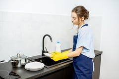 Pratos de lavagem da mulher em casa fotografia de stock