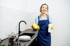Pratos de lavagem da mulher em casa foto de stock
