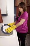 Pratos de lavagem da mulher gravida fotos de stock