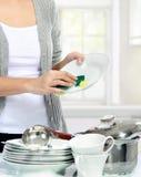 Pratos de lavagem da mulher na cozinha Fotografia de Stock