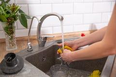 Pratos de lavagem da mulher na cozinha Feche acima da mão da mulher imagens de stock royalty free