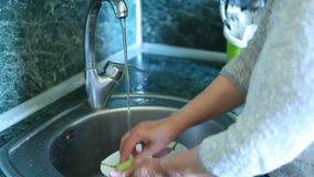 Pratos de lavagem da mulher na cozinha verde do projeto filme