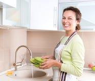 Pratos de lavagem da mulher nova fotos de stock