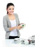 Pratos de lavagem de sorriso da mulher imagem de stock royalty free