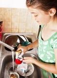 Pratos de lavagem do adolescente em sua cozinha Foto de Stock Royalty Free