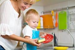 Pratos de lavagem do filho da mãe e da criança na cozinha doméstica fotos de stock royalty free