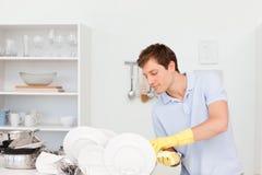 Pratos de lavagem do homem imagens de stock