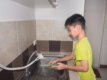 Pratos de lavagem do menino adorável da criança na cozinha doméstica Havi da criança imagem de stock