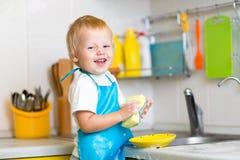 Pratos de lavagem do menino da criança na cozinha fotos de stock royalty free