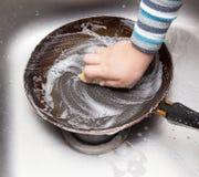 Pratos de lavagem do menino na cozinha foto de stock royalty free