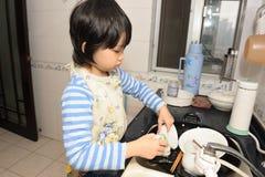 Pratos de lavagem do miúdo asiático Imagens de Stock Royalty Free