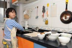 Pratos de lavagem do miúdo asiático fotografia de stock