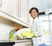Pratos de lavagem felizes da mulher nova foto de stock