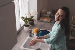 Pratos de lavagem de sorriso da jovem mulher na cozinha na frente de uma janela com as flores em uns potenciômetros na luz macia  imagem de stock