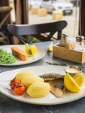 Pratos de peixes com papa de aveia do painço, tomate, fatia do limão e molho de camarão no restaurante Foto de Stock