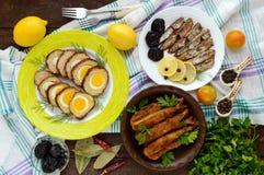 Pratos de peixes: Os peixes brancos rolam enchido com ovos, arenques pequenos feitos casa, badejo fritado Fotos de Stock Royalty Free