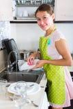 Pratos de secagem da mulher na cozinha imagem de stock royalty free